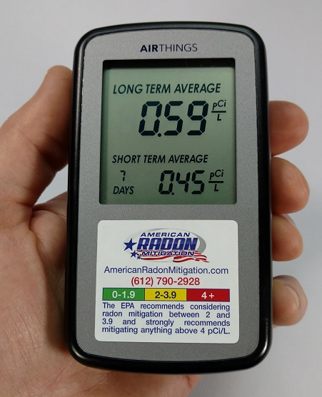 Airthings Home Digital Radon Monitor in hand.