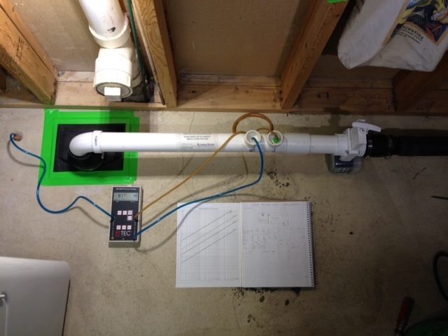 Pitot tube is taped to the floor over the suction point. A shop vac is used to draw air from the suction point.