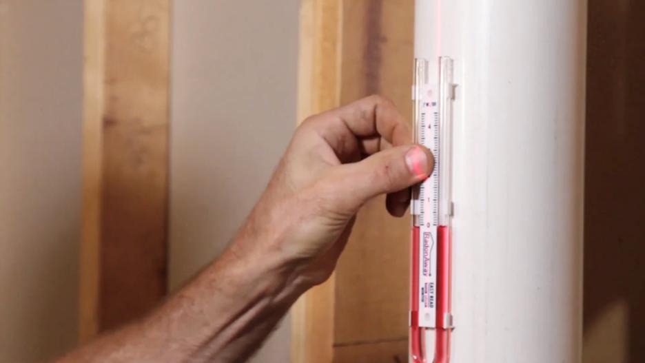 hand holding u-tube radon manometer on radon mitigation pipe