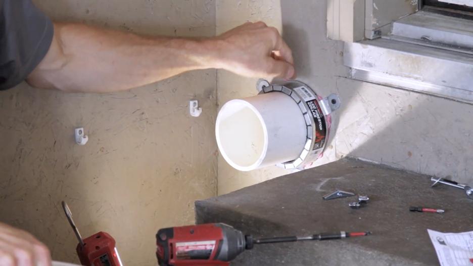 Hand installing a Firestop Collar on a garage wall