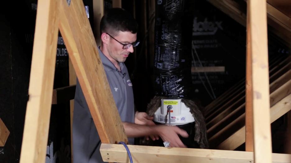 Jesse Green installing a Fantech rn4 ec radon fan in an attic.