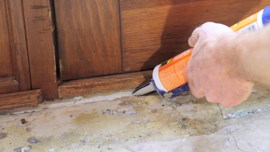Using a caulk gun to apply Radon Sealant to a floor-to-wall joint at a basement walkout door.