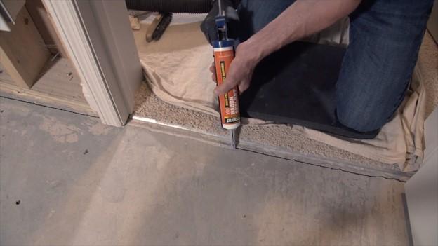 Sealing cracks in the floor with low-VOC radon sealant to increase radon system efficiency
